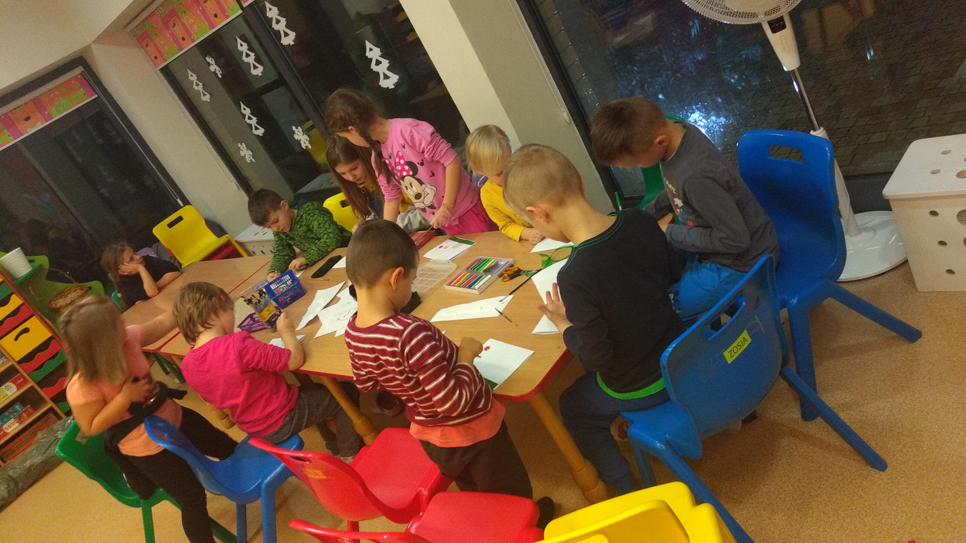 dzieci tworzące obrazki z wykorzystaniem różnych technik plastyczny : flamastry, kredki , farby, ozdoby z koralików