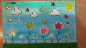 obrazek wykonany na kartce z bloku rysunkowego farbami i ozdobiony koralikami, przedstawia łąkę z kwiatkami i nad nią niebo pełne obłoków