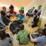 Grupa dzieci na hali sportowej układa piankowe patyki